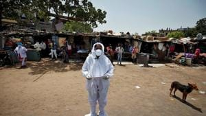 A health worker wearing a protective gear announces names of people who were tested positive for the coronavirus disease (COVID-19) and will be taken to a quarantine facility, during an extended nationwide lockdown to slow the spreading of the disease, at a slum area in India.(REUTERS)