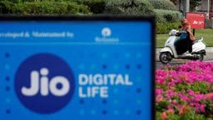 A woman rides her scooter past advertisements of Reliance Industries' Jio telecoms unit, in Ahmedabad, India, July 5, 2018. REUTERS/Amit Dave/Files(Reuters File photo)