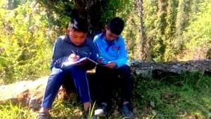 Students studying at a hilltop in Bangaan region of Uttarkashi near Himachal Pradesh border where they get proper mobile connectivity.(HT Photo)