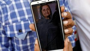Shahid Ahmed holds his mobile phone displaying photo of his mother Irshad Begum, 72, who was killed in a plane crash, outside a morgue in Karachi, Pakistan.(Reuters)