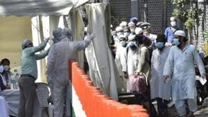People who took part in a Tablighi Jamaat event in March are checked by a health team before being taken to a quarantine facility in this file photo.(Ajay Aggarwal/HT Photo)