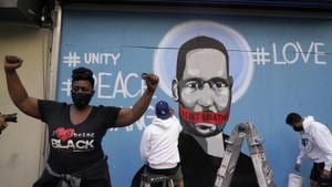A woman gestures while a mural with an image of George Floyd is painted in the background during a rally against the death in Minneapolis police custody of George Floyd, in Los Angeles, California, US.(REUTERS)
