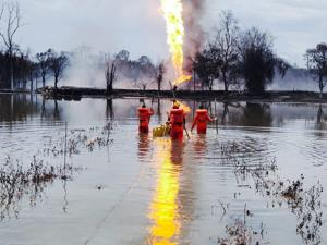 Personnel from NDRF during a search operation for two OIL employees at a pond near a blazing gas well in Assam's Tinsukia district.(NDRF)