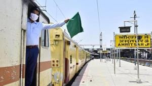 A railway guard waves the green flag aboard a Jaynagar Shaheed Express train at the Amritsar Junction as Indian Railways expand operations under lockdown on Monday.(Sameer Sehgal/HT Photo)