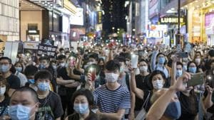 Demonstrators wearing protective masks shine lights from their smartphones during a protest in the Causeway Bay district of Hong Kong, China on Friday.(Bloomberg)