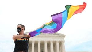 Joseph Fons holding a Pride Flag, stands in front of the US Supreme Court building after the court ruled that a federal law banning workplace discrimination also covers sexual orientation, in Washington, DC.(REUTERS)