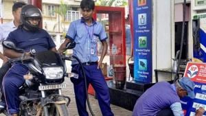 File photo: A fuel station attendant fills out the prices on board, in Guwahati.(PTI)