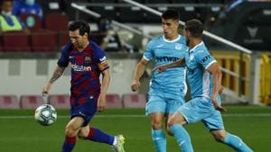 FC Barcelona's Lionel Messi, left, vies for the ball during the Spanish La Liga soccer match between FC Barcelona and Leganes at the Camp Nou stadium in Barcelona, Spain, Tuesday, June 16, 2020. (AP Photo/Joan Montfort)(AP)