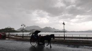A horsecart is seen in the backdrop of Anna Sagar Lake with dark monsoon clouds in the sky, in Ajmer , Rajasthan.(ANI)