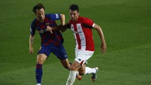 Barcelona's Ivan Rakitic, left, vies for the ball with Athletic Bilbao's Mikel San Jose during the Spanish La Liga soccer match between FC Barcelona and Athletic Bilbao at the Camp Nou stadium in Barcelona, Spain, Tuesday, June 23, 2020.(AP)