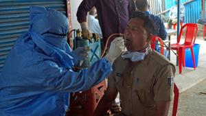 A health worker collect swab sample of a police personnel for Covid-19 test in Bhubaneswar.(ANI)