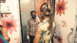 A CSW thermal scans a man before he enters her residence.(Pratham Gokhale/HT Photo)