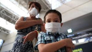 A child and his grandmother wear face masks as they hold their arms after receiving a vaccine as part of the start of the seasonal flu vaccination campaign as a preventive measure due to the outbreak of coronavirus disease (Covid-19), in Santiago, Chile.(REUTERS)