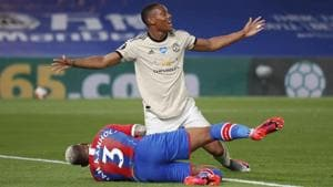 Manchester United's Anthony Martial celebrates scoring their second goal as Crystal Palace's Patrick van Aanholt lies injured.(Pool/REUTERS)