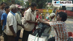 Three times a week, after winding up his fish trade for the day, Rao returns home on his Scooty to pick up food packets.(HT Photo)