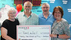 Tom Cook and Joe Feene and their families collecting the prize.(YouTube/Wisconsin Lottery)