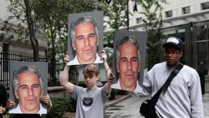 Demonstrators hold signs aloft protesting against Jeffrey Epstein.(REUTERS)