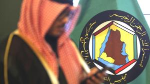 A man looks at his mobile phone in front of the flag of the Gulf Cooperation Council, GCC, in Kuwait City.(AP)