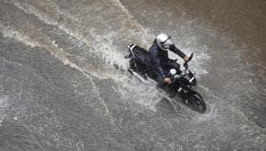 A motorist wades through a water logged road near Rao Tularam Flyover following heavy rain in New Delhi.(Vipin Kumar/HT Photo)