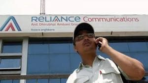 A man talks on a mobile phone in front of an advertisement for Reliance Communications.(Reuters File Photo)