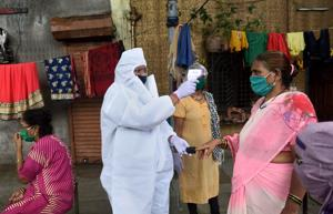 A health care worker checks the temperature of a woman in Mumbai this file photo.(Satish Bate/HT Photo)