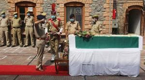 A senior police officer pays tribute to a slain colleague during a wreath laying ceremony at District Police Lines in Srinagar on Sunday.(Waseem Andrabi/HT PHOTO)