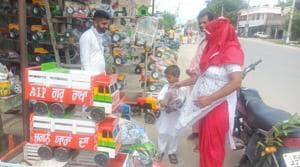 A shopkeeper shows a young customer and his parents a wooden tralla or truck.(HT photo)