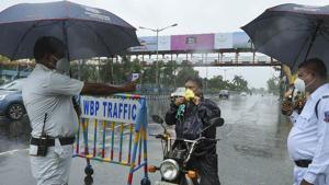 Kolkata: A police constable uses a thermal screening device on a commuter amid rain during the biweekly lockdown in the wake of Covid-19 pandemic.(PTI)