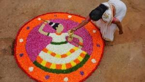 A Keralite woman makes 'Pookalam' (flower rangoli) on the occasion of Onam festival, Chikmagalur in Karnataka.(PTI)