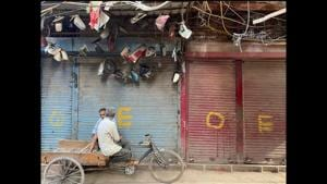 Two rickshaw pullers enjoying a tête-à-tête in Old Delhi's Chatta Sheikh Mangloo against a backdrop of shuttered store fronts marked with O and E, indicating the opening of shops in markets on an odd-even basis during the waning days of the full lockdown in the capital during the month of May. (Mayank Austen Soofi / HT)