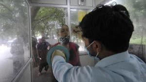 A health worker in an enclosed kiosk collects swab samples for coronavirus testing, at Sector 30 District Hospital, in Noida, India, on Friday, September 04, 2020.(Sunil Ghosh / Hindustan Times)