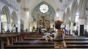 A church usher sprays disinfectant on pews to curb the spread of the coronavirus before a Sunday mass at the Holy Cross Cathedral in Lagos, Nigeria on August 30, 2020.(AP Photo)