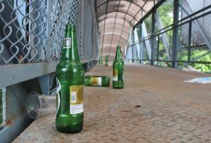 Beer bottles, waste lie scattered on a foot overbridge in Mohali.(HT Photo)