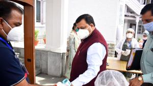 Security personnel check the body temperature of rural development and panchayatiraj minister Virender Kanwar before going to attend the monsoon session in Shimla on Monday.(Deepak Sansta / HT)