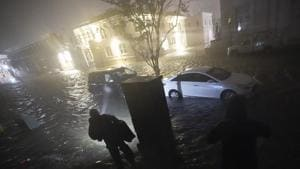 People use flashlights as they walk on flooded streets in search of their vehicle, Wednesday, Sept. 16, 2020, in Pensacola, Fla. Hurricane Sally made landfall Wednesday near Gulf Shores, Alabama,.(AP File Photo)