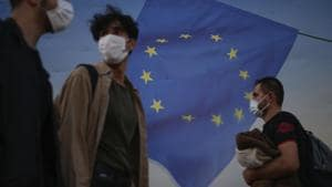 Backdropped by a poster with a European Union flag, people, wearing masks to help protect against the spread of coronavirus, walk in Istanbul. Image used for representational purpose.(AP)