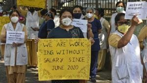 Medical workers show banners during protest to demanding their unpaid salary of four months, outside Hindu Rao Hospital, at Malka Ganj in New Delhi on Wednesday, October, 2020.(Biplov Bhuyan/HT PHOTO)