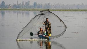 A fisherman casts his net in the Dal Lake as a woman rows the boat, in Srinagar, on October 11, 2020. (PTI Photo/S. Irfan)(PTI)