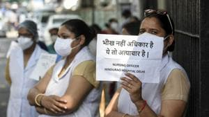A medical worker shows a banner during protest to demanding their unpaid salary of four months, outside Hindu Rao Hospital, at Malka Ganj, in New Delhi.(Biplov Bhuyan/HT PHOTO)