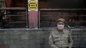 A security person sits wearing a mask outside a temple in Guwahati.(AP)