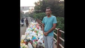 Chandra Kishore Patil standing beside bags of waste.(Twitter)