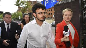 Arsalan Tariq Khawaja, center, is seen at Parramatta Police Station in Sydney, Tuesday, Dec. 4, 2018.(AP)