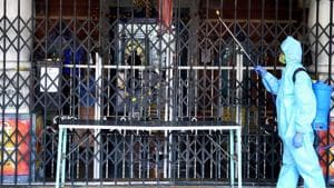 An employee, wearing a PPE kit, sanitizes the premises of a Hindu temple in Mumbai.(PTI)