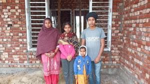 Victim Jagmail Singh's wife Manjit Kaur along with her three children at her under construction house at Dhandiwal village of Sangrur.(HT Photo)