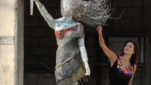 Lebanese artist, Hayat Nazer, poses near her statue made entirely out of broken glass and debris of the August 4 port explosion, during an interview with Reuters in Beirut, Lebanon November 10, 2020.(REUTERS)