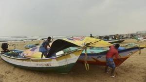 Fishermen cover their boats at Marina Beach during heavy rain, triggered by Cyclone Nivar,in Chennai.(PTI)