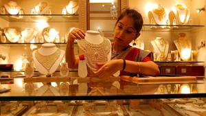 A saleswoman displays a gold necklace inside a jewellery showroom in Kolkata in this file photo.(Reuters Photo)