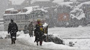 People trudging through snow in Gund area of Ganderbal district on Wednesday.(Waseem Andrabi/ HT)