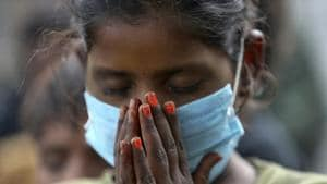 An underprivileged child wearing face mask as a precaution against the coronavirus participates in morning prayer at the Sangharsh Vidya Kendra school at a slum area on the outskirts of Jammu on Wednesday.(AP)