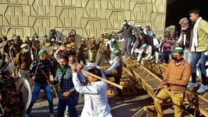 Members of the Bharatiya Kisan Union break through barricades at UP Gate, at the Ghaziabad border with Delhi.